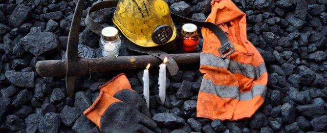mining accident victim vigil with gloves, hardhat, pic, and candles