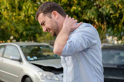 man feeling neck pain after car accident
