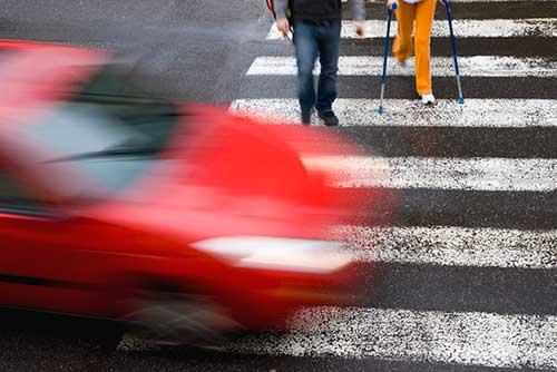red car speeding past pedestrians crossing street at crosswalk