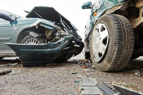 two green cars crash on urban Denver street