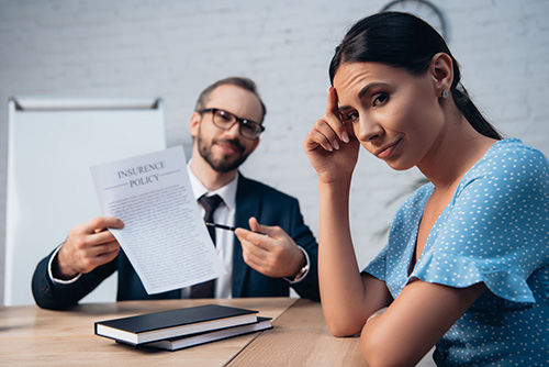 woman looking away in disagreement from insurance company attorney